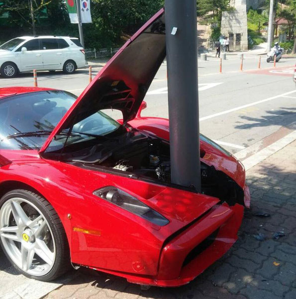 Cột điện nằm kẹt giữa đầu xe của chiếc Ferrari Enzo màu đỏ.