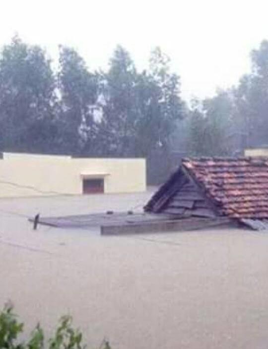 Nước mưa dâng cao gần đến mái nhà của người dân. Ảnh: FB Tiến Nghĩa