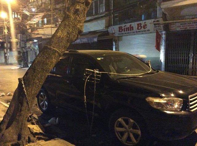 Có chủ xe còn cẩn thận hơn khi buộc dây xích nối với gương và cây bên đường.