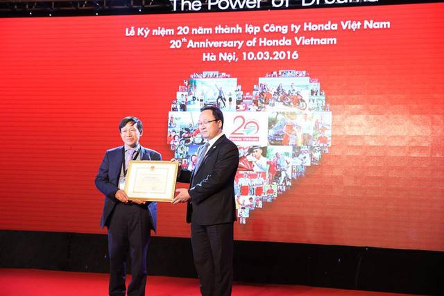Ông Khuất Việt Hùng, Phó chủ tịch Ủy ban An toàn giao thông Quốc gia, trao tặng bằng khen cho đại diện Honda Việt Nam.