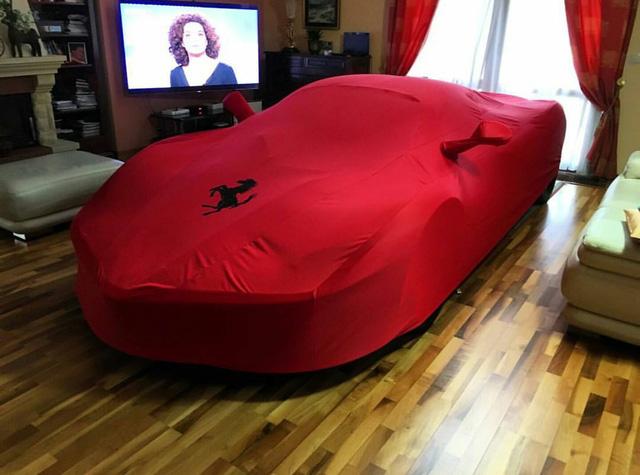 """Trong hình ảnh, chiếc siêu xe Ferrari LaFerrari lú thì được phủ bạt lúc """"ở trần"""". Chiếc xe nằm ngay ngắn giữa kệ Tivi và chiếc ghế sofa trong phòng khách. Bên cạnh đó, còn có lò sưởi. Nhìn chung, phòng khách của """"thánh cuồng"""" tại Slovakia có vẻ khá chật chội để trưng bày chiếc siêu xe đắt tiền như Ferrari LaFerrari."""