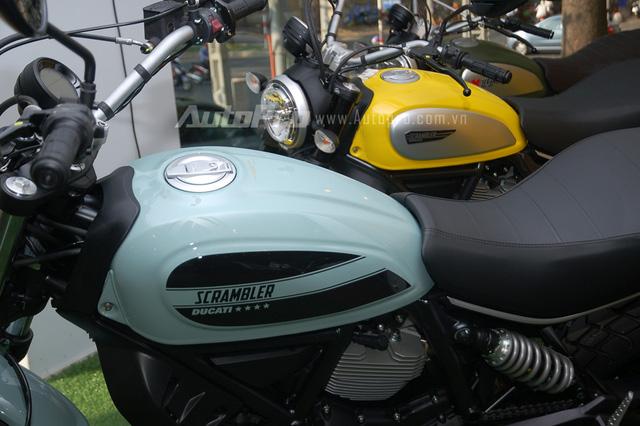 So với đàn anh 800 phân khối màu vàng đứng bên cạnh, Ducati Scrambler Sixty2 có thiết kế không thay đổi nhiều. Điểm khác biệt nằm ở ốp bình xăng với 2 sọc đen cỡ lớn cùng dòng chữ Scrambler nằm chính giữa, giúp mẫu mô tô 400 phân khối thu hút nhiều ánh nhìn.