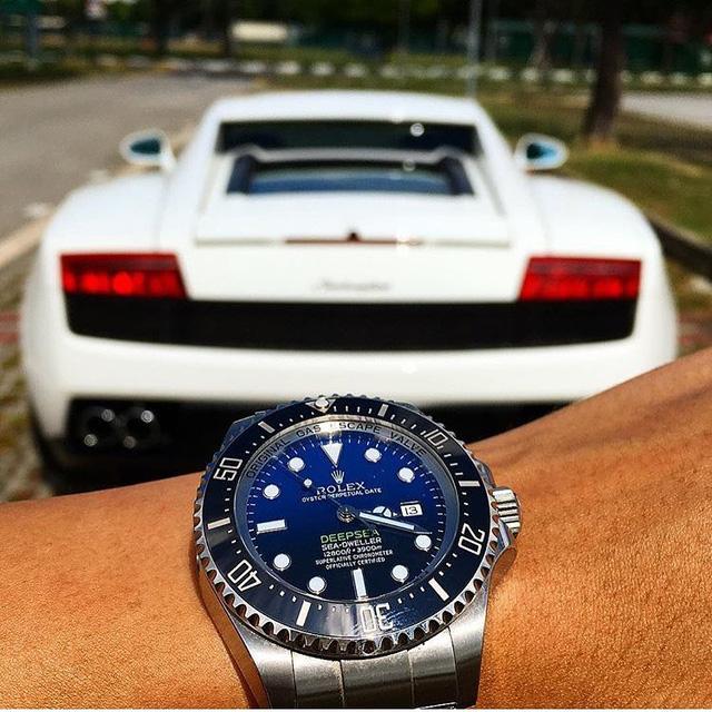 """Chiếc đồng hồ Rolex Deepsea bên siêu xe Lamborghini. Đây là chiếc đồng hồ nổi bật với khả năng chịu nước tới độ sâu 3.900m và được trang bị vỏ Oyster 44mm. Chiếc Rolex này đáp ứng yêu cầu khắt khe nhất của thợ lặn chuyên nghiệp. Đạo diễn James Cameron đã từng đeo Rolex Deepsea trong chuyến thám hiểm rãnh Marina. Để đánh dấu sự hợp tác giữa Rolex và Cameron, dòng chữ """"DEEPSEA"""" trên mặt đồng hồ có màu xanh lá cây giống với màu con tàu của nhà thám hiểm. Chiếc Rolex này có giá khoảng 13,000 USD (khoảng 300 triệu đồng)."""
