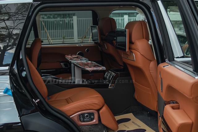 Đối với những chiếc SUV siêu sang như Range Rover SVAutobiography, hàng ghế sau chính là nơi moi tiền của khách hàng. Ghế sau tích hợp thêm đệm đỡ bắp chân và bàn làm việc mini ốp gỗ sang trọng tích hợp thêm khay đựng ly hay hộc lạnh chứa đồ.