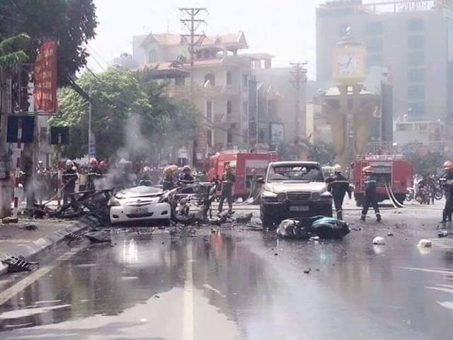 Chiếc taxi màu trắng đỗ sát vỉa hè cháy nổ dữ dội. Chiếc ô tô bên cạnh và 1 xe máy lưu thông lại gần cũng bị liên đới.