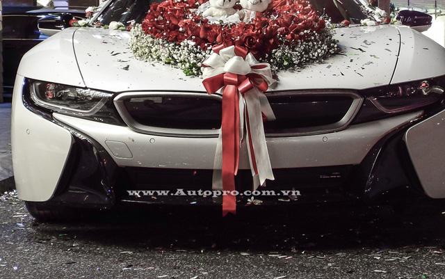 Ở phần đầu xe chiếc BMW i8 trở nên lộng lẫy khi được trang trí bó hoa cưới cỡ lớn trên nắp capô, chính giữa có cặp gấu bông xinh xắn. Bên cạnh đó còn có nơ cưới được kéo dài từ mũi xe đến cản va trước khá bắt mắt.