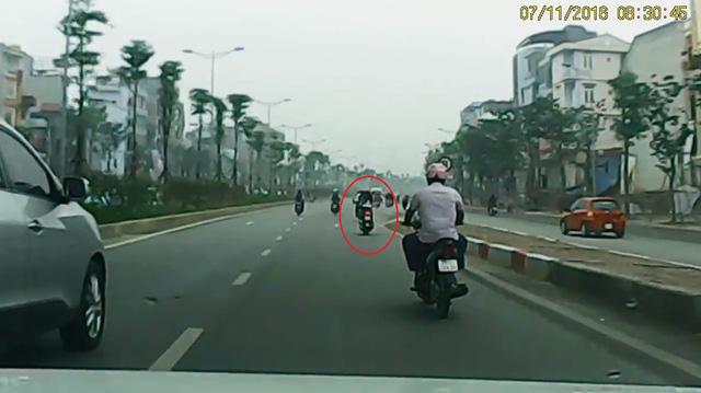 Các phương tiện xuống cầu vượt. Cô gái trẻ đi trước người đàn ông. Ảnh cắt từ video