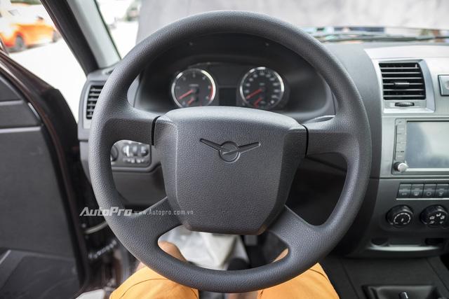Vô-lăng bốn chấu ốp nhựa đen sần của Uaz Pickup và chẳng có nút điều khiển nào được tích hợp.