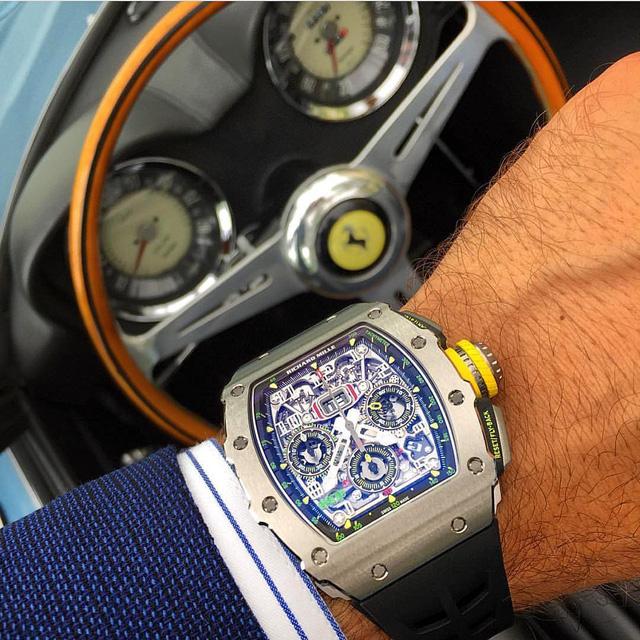 Một đại diện đến từ Richard Mille trong bài viết lần này, đó là chiếc đồng hồ RM 11-03 khoe bộ máy tourbillion đầy mê hoặc của mình bên trong buồng lái siêu xe Ferrari Spyder. RM 11-03 là một tổng thể gồm những chi tiết được truyền cảm hứng bởi những chiếc xe đua: núm crown làm bằng titanium cấp độ 5 mang dáng dấp của chiếc lốp và bánh xe công thức 1; nút bấm có các đường khía gợi nhớ tới bề mặt của những chiếc pedals và có phần vỏ bọc làm bằng vật liệu quen thuộc với công thức 1, đó là NTPT Carbon - vật liệu siêu bền, siêu cứng và siêu nhẹ đã trở thành một đặc trưng trong những thiết kế của Richard Mille.
