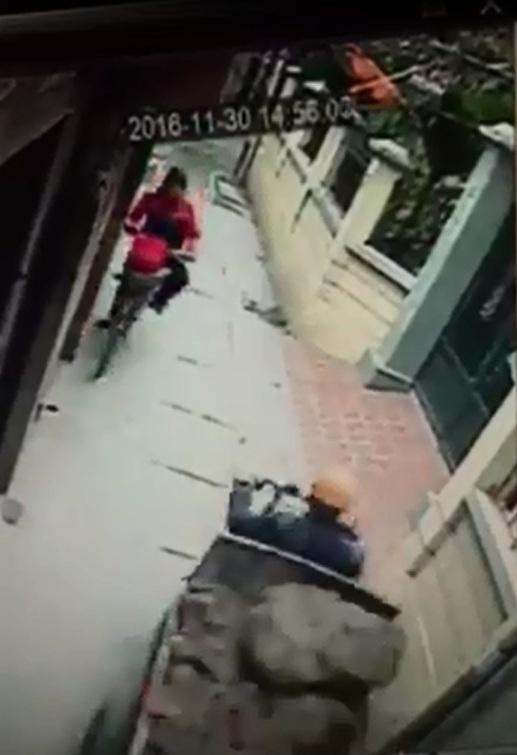 Người phụ nữ đạp xe, chở bé trai phía sau đi trong ngõ hẹp. Ảnh cắt từ video