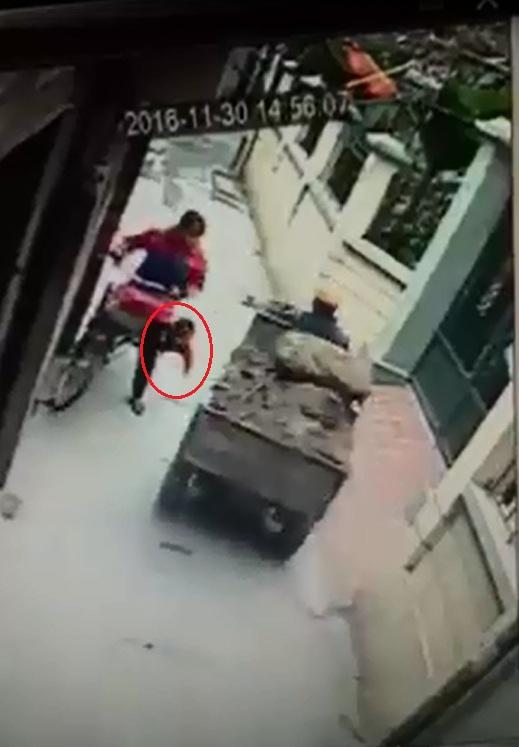 Khi gặp xe công nông, người phụ nữ bị giật mình và loạng choạng khiến bé trai rơi khỏi xe đạp. Ảnh cắt từ video