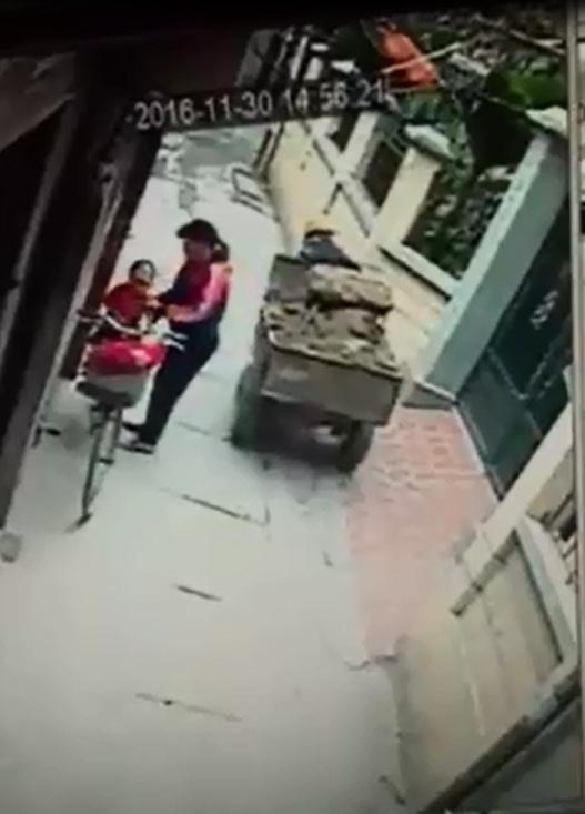 Sau vụ tai nạn, người phụ nữ bế bé trai lên yên xe đạp. Ảnh cắt từ video