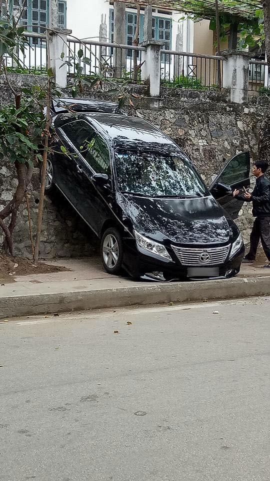 Lào Cai: Lùi quá đà, Toyota Camry gác đuôi lên bức tường - Ảnh 1.