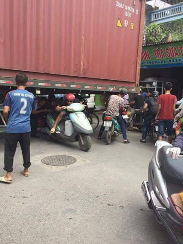 Bất chấp nguy hiểm, người dân thi nhau chui gầm container chắn ngang giữa đường để lưu thông - Ảnh 2.