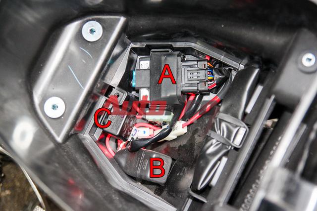 IC và cầu chì tổng được đặt dưới cốp xe tránh nước và bụi bẩn. Để tiếp cận các chi tiết này, chỉ cần mở 1 tấm ốp đơn giản. Các chi tiết này được bắt vào phần cốp xe, do đó, để tiến hành tháo phần cốp, phải tháo tất cả các chi tiết. A: IC, B: rơ-le đề, C: rơ-le xi-nhan.