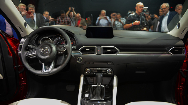 Bước vào bên trong Mazda CX-5 thế hệ mới, người lái được chào đón bằng không gian nội thất mới mẻ nhờ vô lăng 3 chấu, nút bấm khởi động máy, màn hình màu 4,6 inch nằm trong cụm đồng hồ.