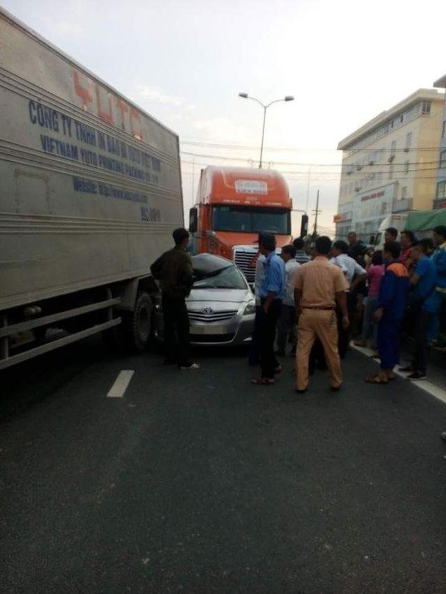 Chiếc Toyota Vios bị kẹp giữa ô tô tải và xe container. Ảnh: Linh Quách