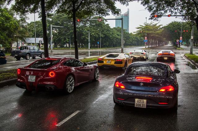 Đoàn siêu xe gồm có 4 chiếc như Lamborghini Aventador LP700-4, Huracan LP610-4, Ferrari F12 Berlinetta và 488 GTB. Ngoài ra, trong đoàn, còn có mẫu xe thể thao mui trần BMW Z4 góp mặt. Trong ảnh, đoàn xe đang dừng chờ đèn đỏ tại đại lộ Nguyễn Văn Linh trước khi vào hầm Thủ Thiêm và nhanh chóng vào cao tốc Long Thành - Dầu Giây để phượt xuống Hồ Tràm.
