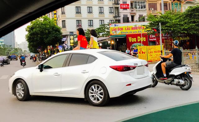 Clip: 2 bé gái ngồi trên cửa sổ trời ô tô chạy giữa phố Hà Nội - Ảnh 2.