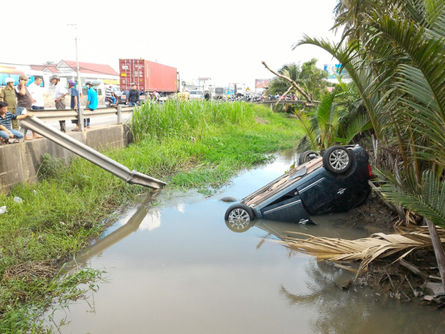 Tiền Giang: Va chạm xe đầu kéo, ô tô ngửa bụng dưới kênh, 5 người thoát chết - Ảnh 1.
