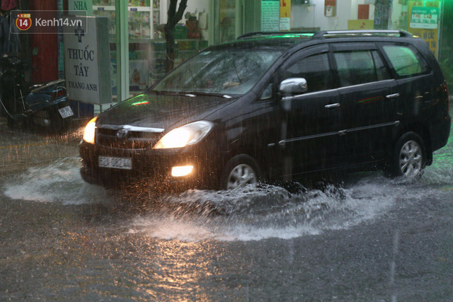 Giữa ban ngày mà Sài Gòn bỗng tối sầm vì mưa lớn, người dân phải bật đèn di chuyển trên đường 1