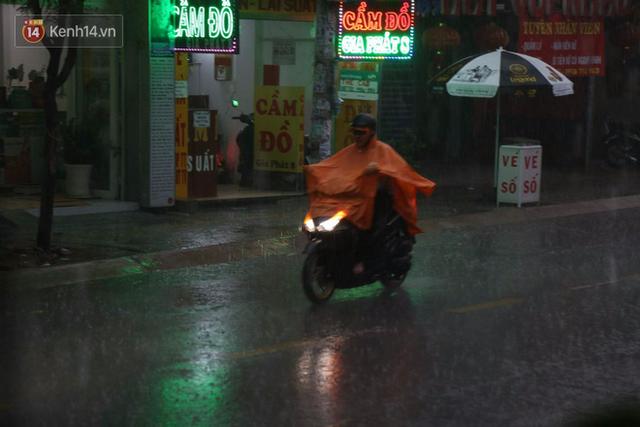 Giữa ban ngày mà Sài Gòn bỗng tối sầm vì mưa lớn, người dân phải bật đèn di chuyển trên đường 2