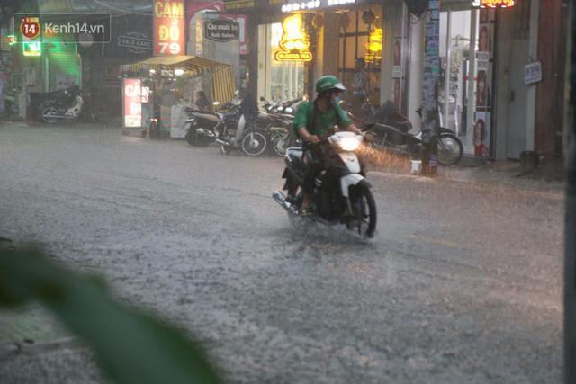 Giữa ban ngày mà Sài Gòn bỗng tối sầm vì mưa lớn, người dân phải bật đèn di chuyển trên đường 4