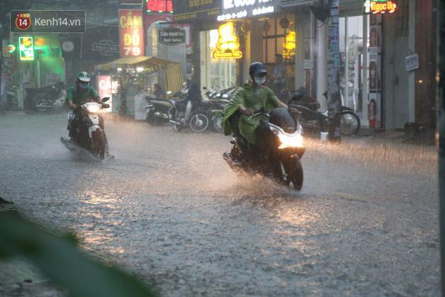 Giữa ban ngày mà Sài Gòn bỗng tối sầm vì mưa lớn, người dân phải bật đèn di chuyển trên đường 5