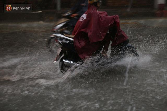 Giữa ban ngày mà Sài Gòn bỗng tối sầm vì mưa lớn, người dân phải bật đèn di chuyển trên đường 6