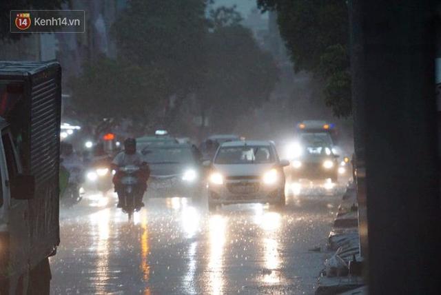 Giữa ban ngày mà Sài Gòn bỗng tối sầm vì mưa lớn, người dân phải bật đèn di chuyển trên đường 9