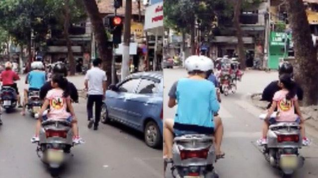 """Clip: Mẹ dán logo """"đã uống rượu bia, không lái xe"""" rồi chở con gái đầu trần vượt đèn đỏ trên đường phố Hà Nội khiến nhiều người bức xúc"""