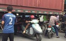 Bất chấp nguy hiểm, người dân thi nhau chui gầm container chắn ngang giữa đường để lưu thông