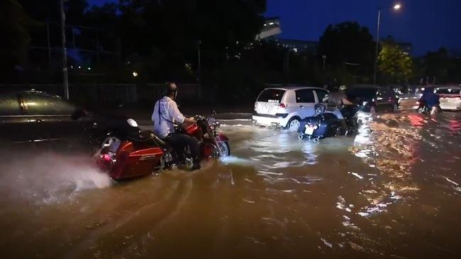 Xem cảnh cặp đôi mô tô Harley-Davidson lội bì bõm trên đường ngập tại Hà Nội